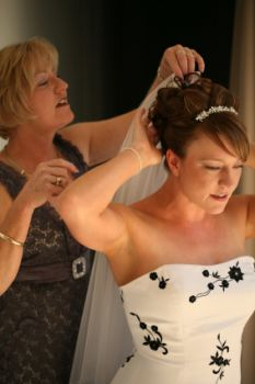 Mother of the bride helping her daughter prepare for her wedding day